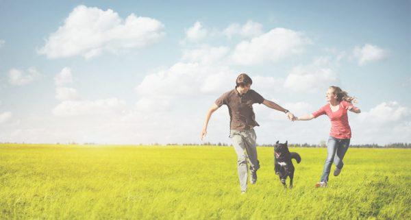 Boy, dog and girl running